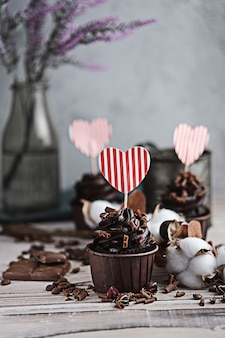 Several muffins or cupcakes with chocolate shaped cream at white table. a card in the form of a heart for st. valentine's day. a woman's hand crumbles grated chocolate onto a cake.