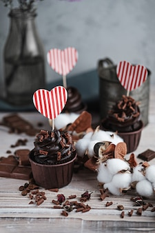 Several muffins or cupcakes with chocolate shaped cream at white table. a holiday card in the form of a heart for st. valentine's day in one of them.