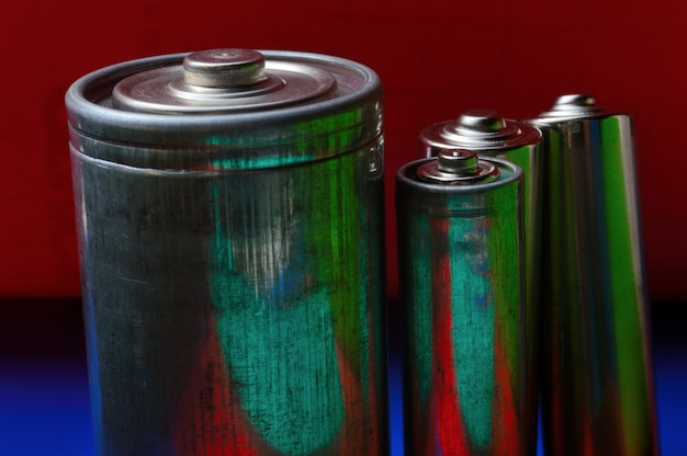 Несколько разноцветных батареек на сине-красном фоне. крупный план.