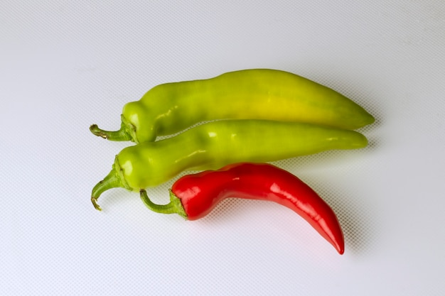 Several multi-colored hot chili peppers on a light background