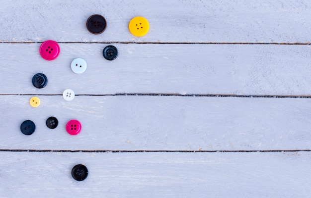 Several multicolored buttons on a wooden background