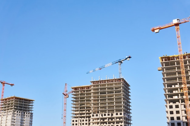 Several multistory blocks of flats under construction with tower cranes against the sky