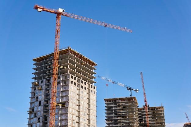 하늘을 배경으로 타워 크레인으로 건설 중인 여러 층의 아파트
