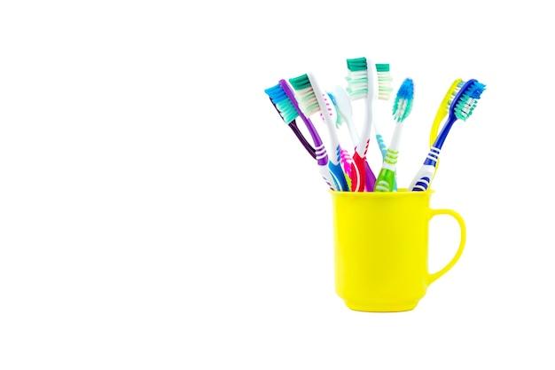 Несколько старых зубных щеток размещены в желтом пластиковом стакане, изолированном на белом фоне.