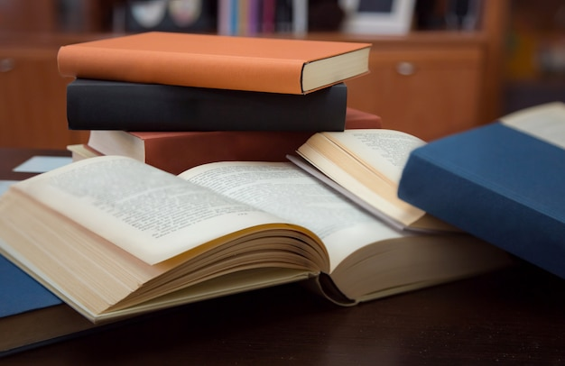 Several open and closed books on wooden table