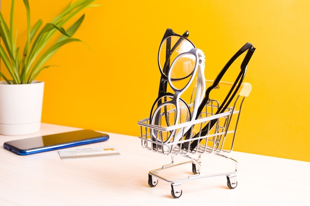 Several pairs of different glasses for vision correction in a small shopping cart on the table