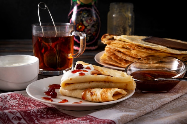 Several pancakes with berries, sour cream and jam on a plate, a mug of black tea on a towel on a dark wooden surface