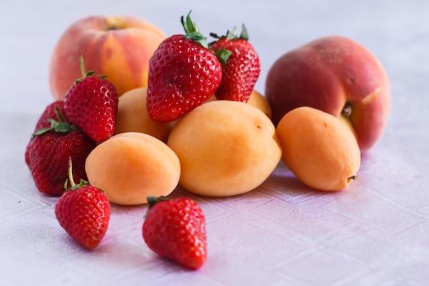 白いテーブルクロスにいくつかの桃、アプリコット、イチゴ