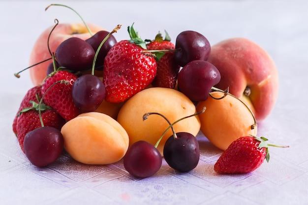白いテーブルクロスにいくつかの桃、アプリコット、チェリー、イチゴ
