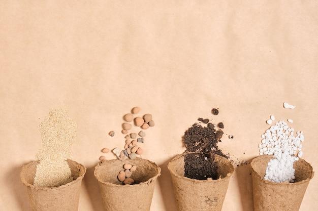 Несколько торфяных горшков с разными ингредиентами для подготовки плодородной почвы для растений, камни для дренажа, перлит, почва для рассады, удобрения для сада