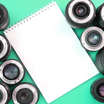 На ярко-бирюзовой стене лежат несколько фотообъективов и белый блокнот. место для текста