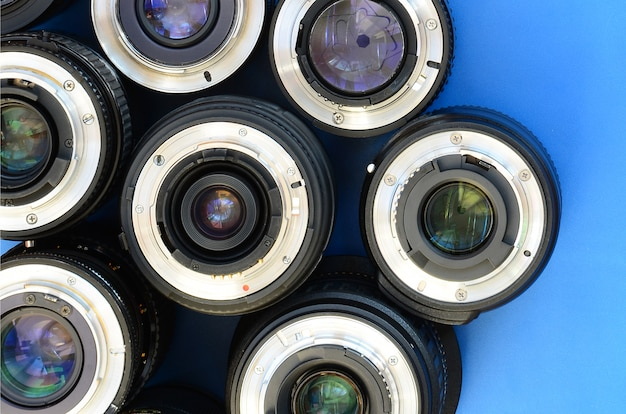 Several photographic lenses lie on a bright blue background. space for text