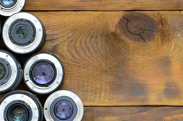 Several photographic lenses lie on a brown wooden background.