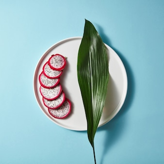 Several pieces of a sliced white pink pitahaya