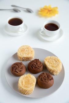 灰色のプレートにクリームと白のお茶のカップとスポンジケーキのいくつかの部分