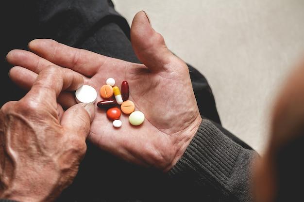 Несколько таблеток в руках пожилого человека