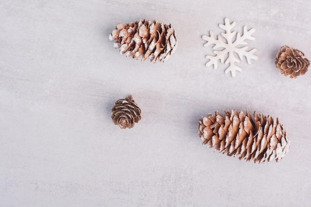 Several pine cones and snowflakes on white table.