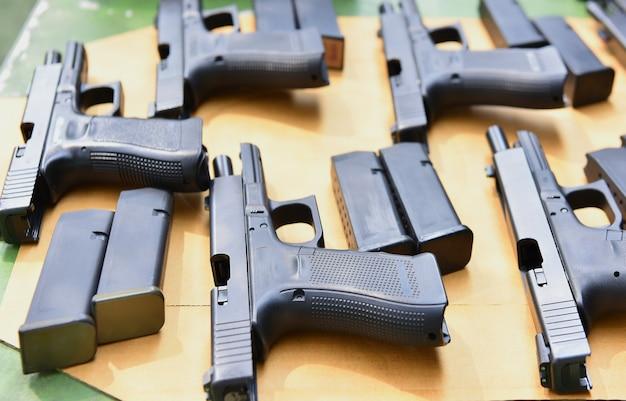 여러 개의 권총이 사격장의 안전한 위치에있는 테이블에 놓여 있습니다.