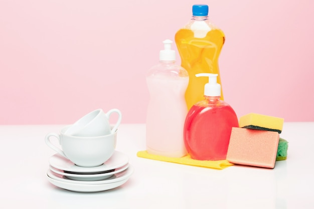 Несколько тарелок, кухонные губки и пластиковые бутылки с натуральным жидким мылом для мытья посуды, используемым для мытья посуды вручную.