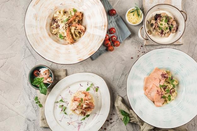 明るい背景でシェフが提供する魚とシーフードのパスタのいくつかのプレート。コピースペースで上から表示します。レストランの食べ物。フラットレイ