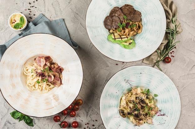 Несколько тарелок мяса и куриной пасты, подаваемые шеф-поваром на светлом фоне. вид сверху с копией пространства. ресторанная еда. flatley
