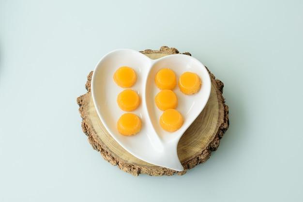 Несколько квиндинов на тарелке в форме сердца. традиционное бразильское сладкое.