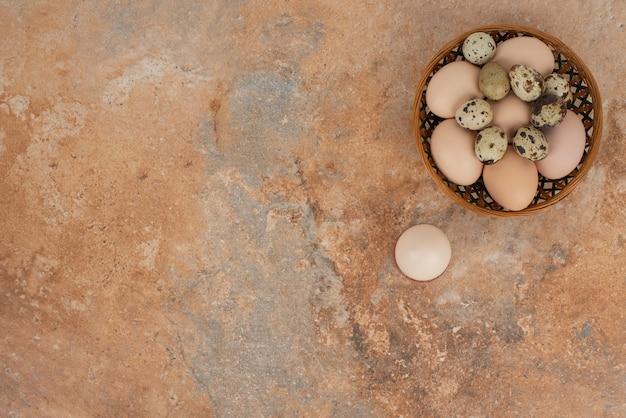 大理石の表面のバスケットにいくつかの生卵