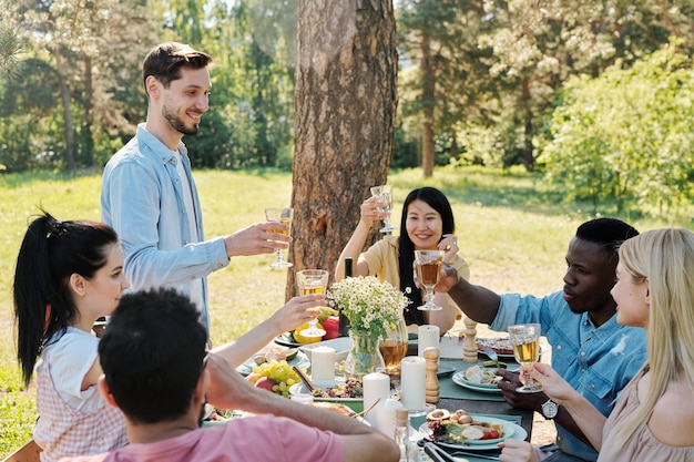 Several restful international friends going to clink with glasses of wine while toasting over served festive table at outdoor dinner under pine tree