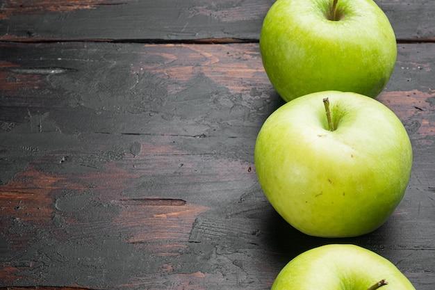 오래된 어두운 소박한 테이블 배경에 여러 익은 녹색 사과 세트, 텍스트 복사 공간