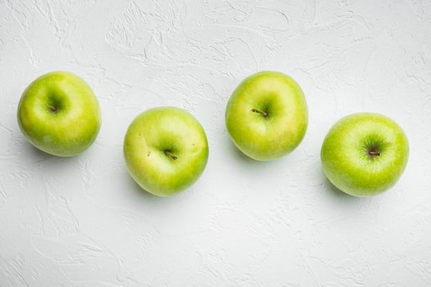 Набор нескольких спелых зеленых яблок на фоне белого каменного стола, плоская планировка, вид сверху