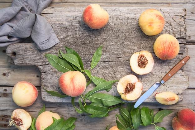Несколько спелых сочных персиков на деревянной поверхности.