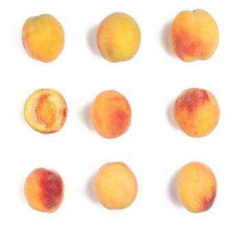 Несколько спелых персиков на белом фоне. один разрезан. вид сверху.