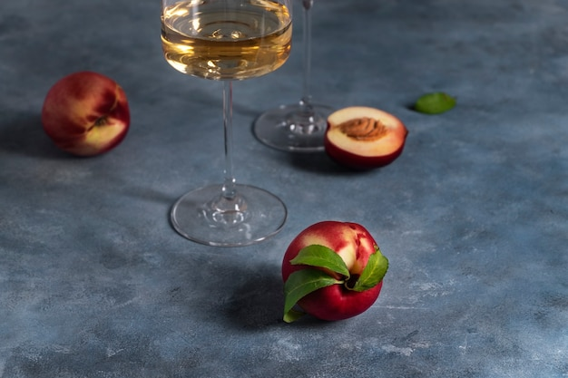 Несколько спелых персиков или нектаринов и бокал белого персикового вина.