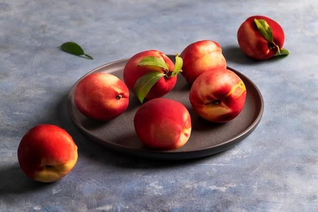 Несколько спелых персиков или нектаринов лежат на черной керамической тарелке.