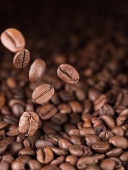 Несколько жареных кофейных зерен падают на кофейные зерна. вертикальный.