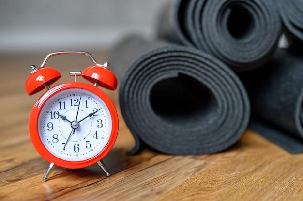 木の床にいくつかの巻かれたヨガまたはフィットネスラバーマットの黒い色と赤い目覚まし時計。スポーツアクセサリー。