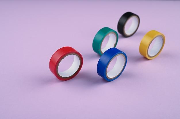 Несколько круглых рулонов цветной пластиковой ленты лежат в ряд.