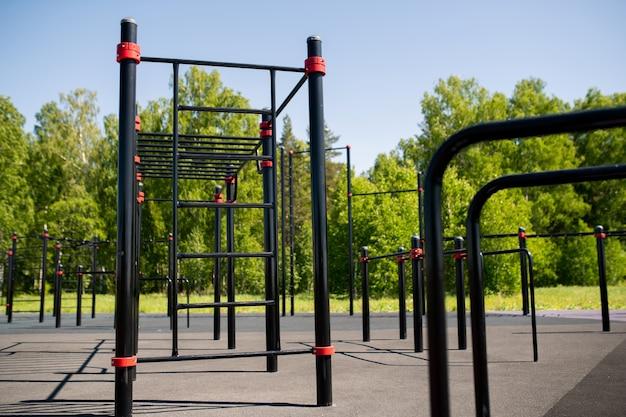 緑の木々とエクササイズするためのバーのある数列の現代的なスポーツ施設
