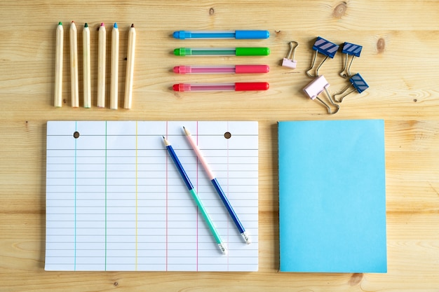Several sets of pens and crayons and group of clips with book in blue cover and lined notebook page with two pencils near by