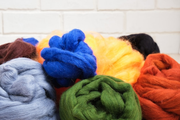 Several skeins of dyed natural sheep wool for felting on the table close-up