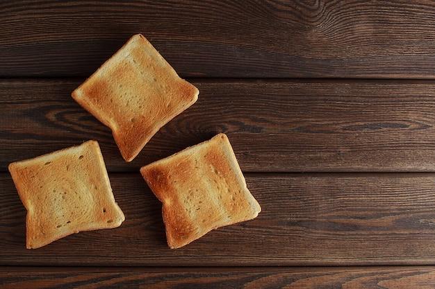 Несколько ломтиков тостов поджаренного хлеба на деревянном темном фоне.
