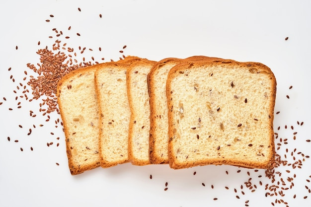 Several slices toast bread with pumpkin, poppy, flax, sunflower, sesame and millet seeds  isolated on white background for proper nutrition. top view, flat lay