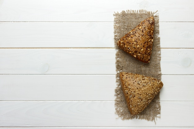 Several small multi grain triangular shaped bread sprinkled with whole sunflower seeds, flax and sesame seeds on a sackcloth