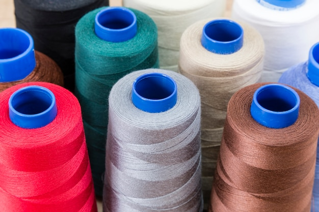 Several spools of thread of different colors and sizes