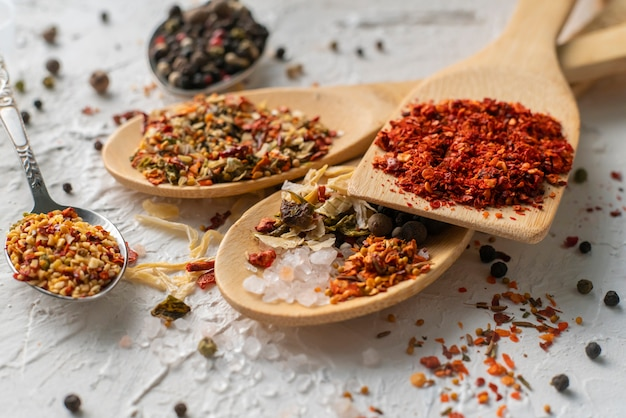 Several spoons with mix variaty of different spices poured on the tables
