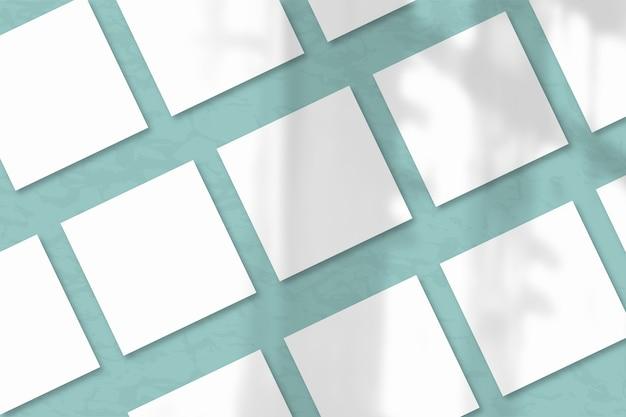 Несколько квадратных листов белой фактурной бумаги на фоне сине-зеленой стены. естественный свет отбрасывает тени из окна. плоская планировка, вид сверху. горизонтальная ориентация