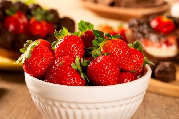 부활절 달걀 배경으로 나무 테이블에 흰색 냄비에 여러 딸기.