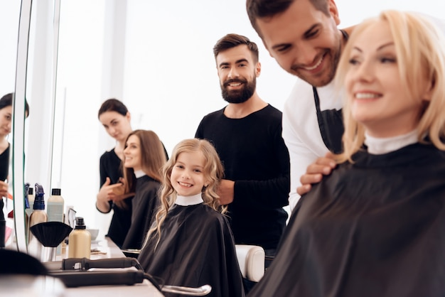 Several stylists make hairstyle for women of different ages.