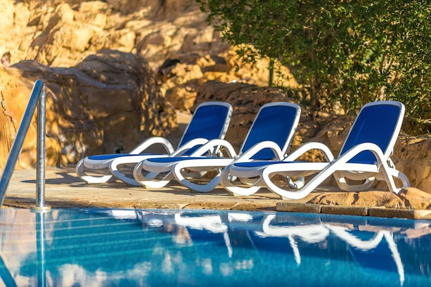 Several of sun loungers by beautiful swimming pool and treess