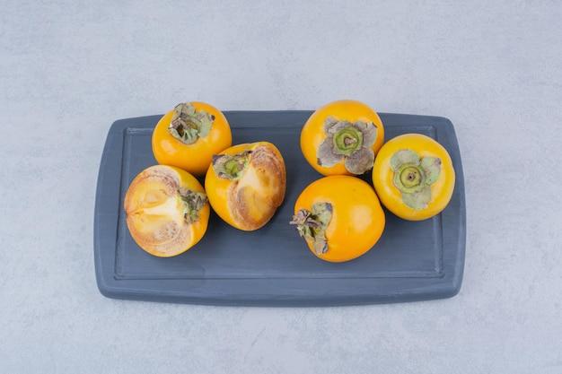 ダークボードにいくつかのおいしい柿。高品質の写真